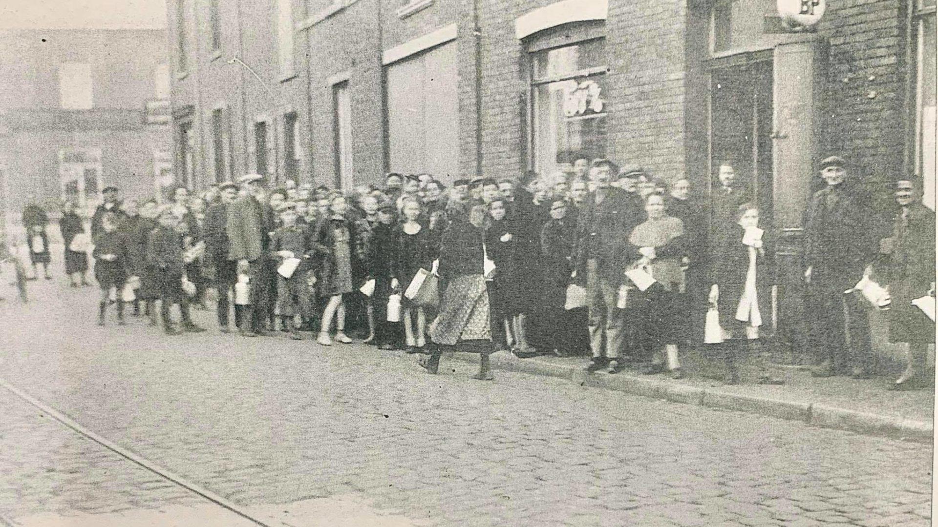 """Ravitaillement. File des personnes venues acheter du lait écrémé au magasin dit du """"Coq de Paille"""", Rue du Général Leman."""